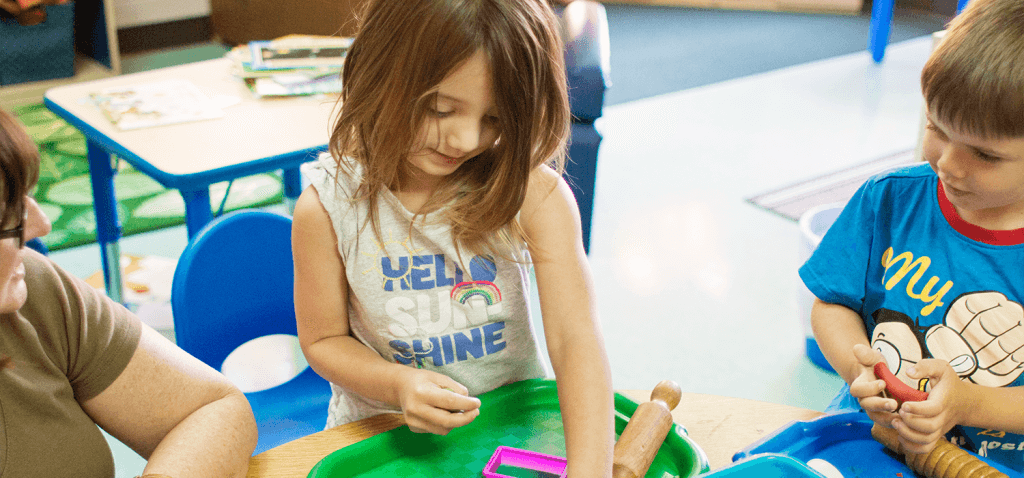 A girl and boy are playing with modeling clay at a table. Beside the girl, a teacher is slightly off camera and appears to be speaking to her.