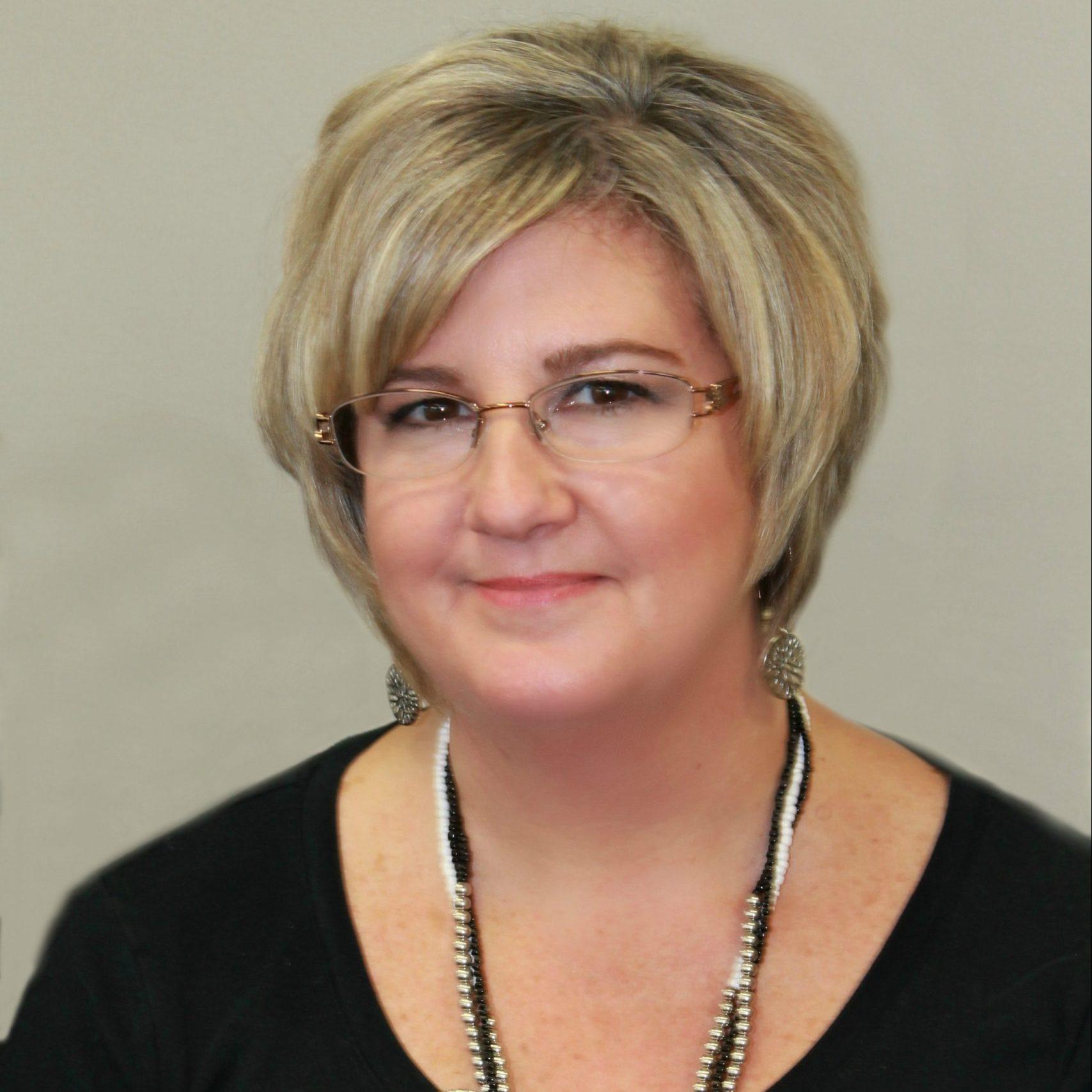 A photo of Lisa wearing a black shirt and smiling at the camera.
