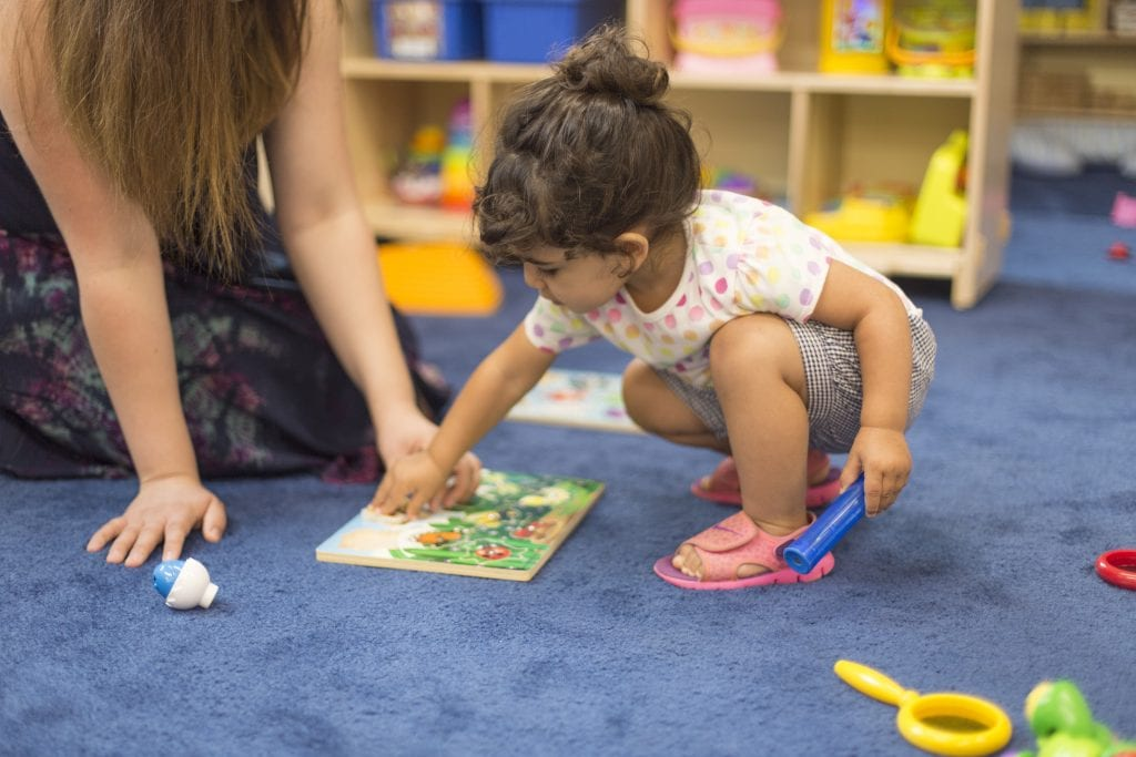 A child is pointing to a picture in a book. Beside her, an adult is ready to turn the page.