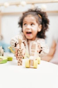 A girl is reaching for a wooden toy on a low table. She is looking off camera with an excited look