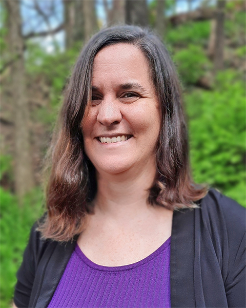 Photo of a woman smiling at the camera wearing a purple shirt with a black jacked standing in front of green trees