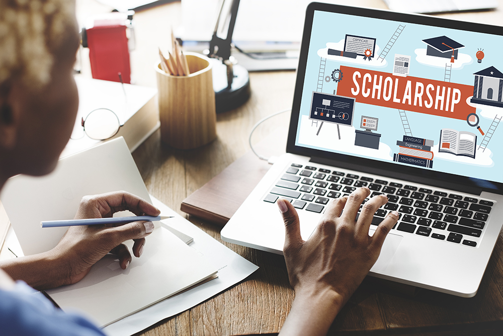 Photo of a laptop computer with the word Scholarship on the screen with a female taking notes and looking at screen.