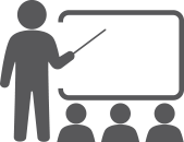 Icon of a teacher pointing at a chalkboard to represent training